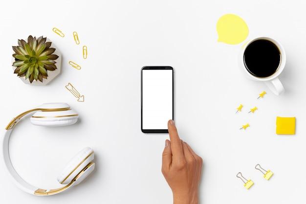 Пустой мобильный телефон на макете современного рабочего пространства