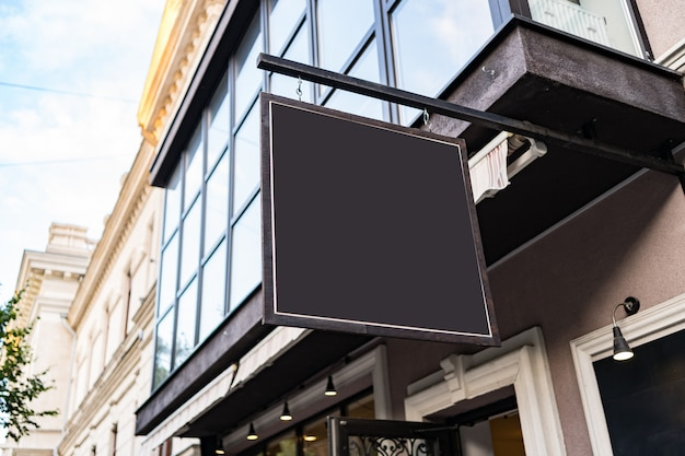 屋外の素敵な建物のカフェ看板のデザインを空白のモックアップ