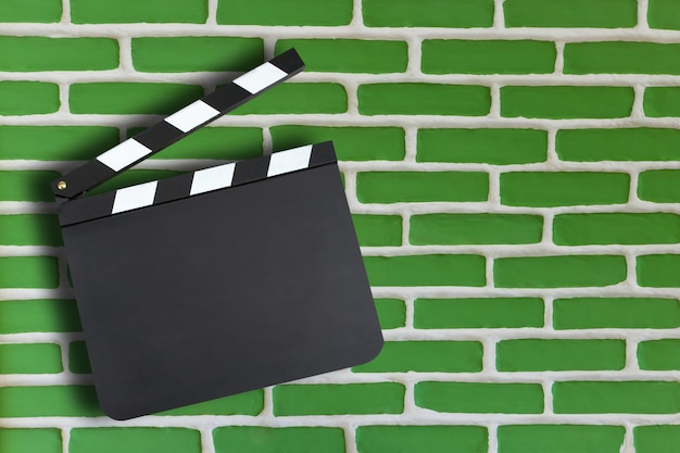 Blank movie production clapper board over brick wall background with copy space
