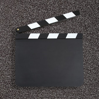 Blank movie production clapper board over dark background with c