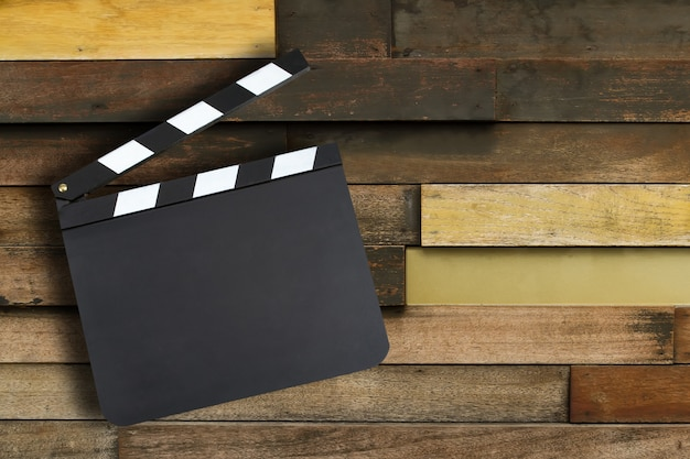 Blank movie production clapper board over vintage wooden wall wi