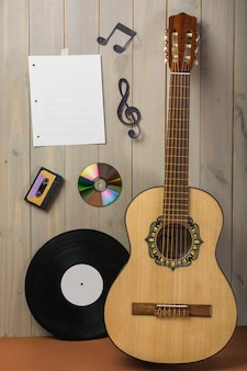 Blank musical page; cassette; compact disc; and musical note stuck on wooden wall with guitar and vinyl record