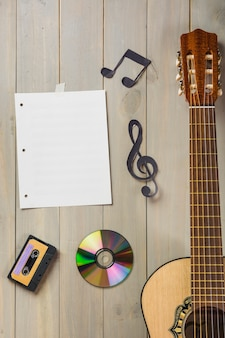 Blank musical page; cassette tape; compact disc; and musical note stuck on wooden wall with guitar