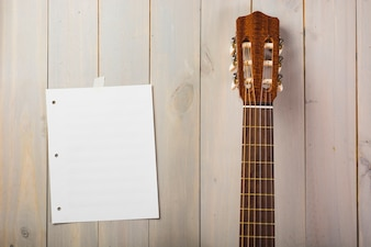 Blank musical page stuck on wooden wall with guitar's head