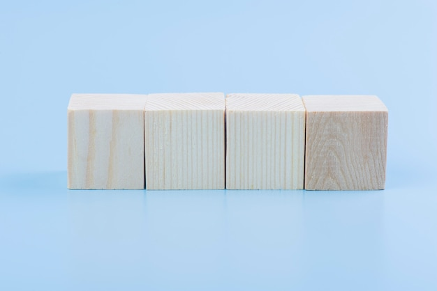 Blank natural wooden cube block on blue background