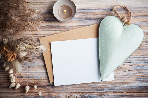 Пустая нота и зеленое декоративное сердце, зажженная ароматическая свеча и сухие цветы на деревенском столе. открытка на свадьбу