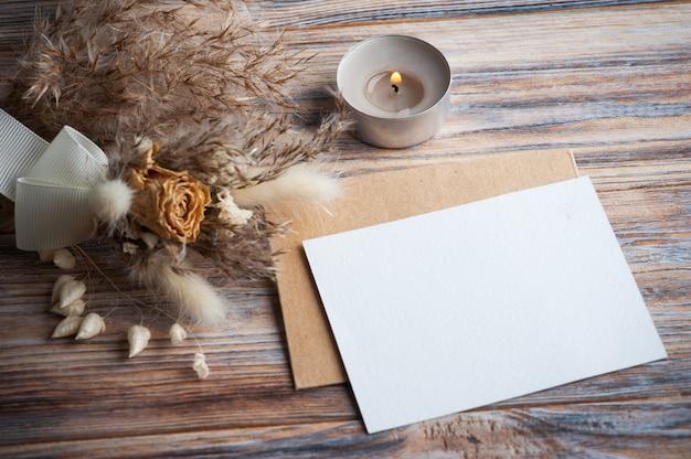 Пустая записка и зажженная ароматическая свеча и сухие цветы на деревенском столе. открытка на свадьбу