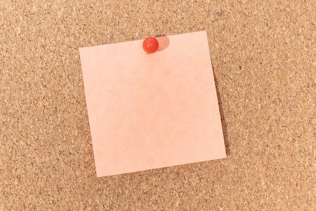 Пустая записка и канцелярская кнопка на пробковой доске. шаблон для текста объявления или рисунков