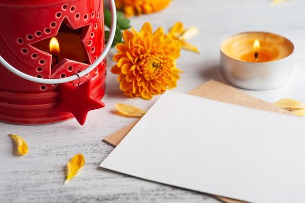 Пустая записка и зажженная красным цветом свеча аромата и цветы на деревенском столе. открытка на праздник