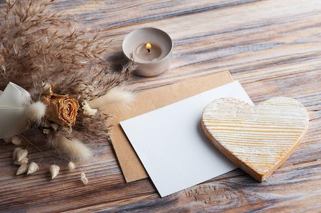 Пустая нота и желтое декоративное сердце, зажженная ароматическая свеча и сухие цветы на деревенском столе. открытка на свадьбу