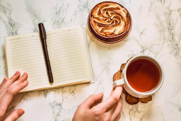 空白のメモ帳お茶とケーキのカップコピースペースのある上面図作業場所プレーニングコンセプトトーン