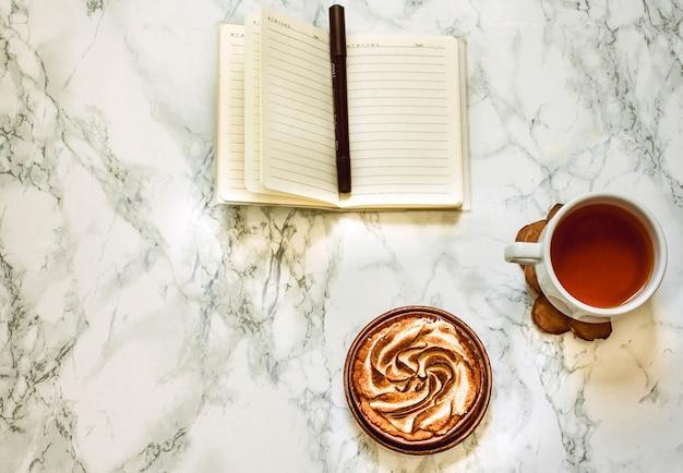 白紙のメモ帳、お茶とケーキ。コピースペースのある上面図。職場。プレーニングのコンセプト。