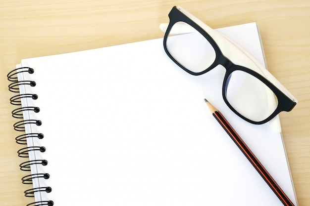 Blank note book paper, eye glasses and pencil on wood background, template
