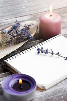 空白のノートブック、紫色のアロマキャンドル、木製のドライラベンダーの花