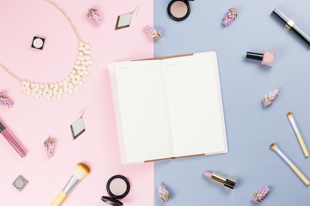 Пустая записная книжка, плоские женские косметические аксессуары на пастельном фоне