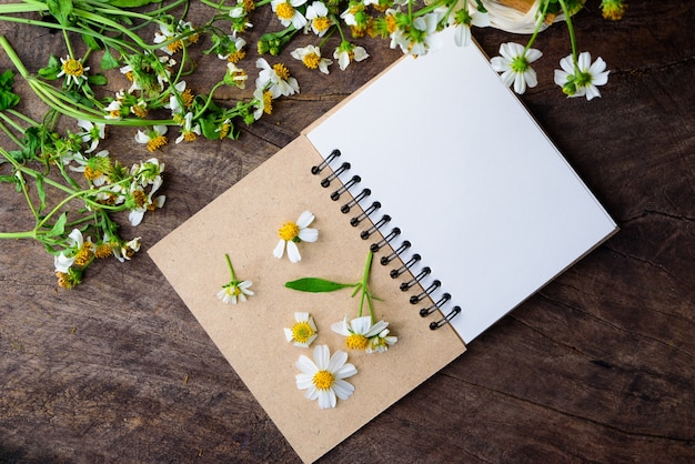 Blank note pad and white flowers on an old wooden board back
