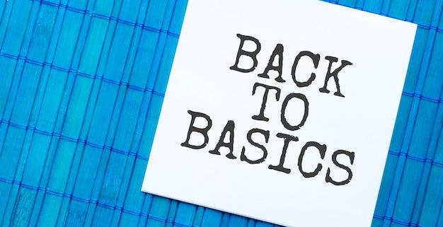 Пустой блокнот с текстом back to basics на синем деревянном фоне