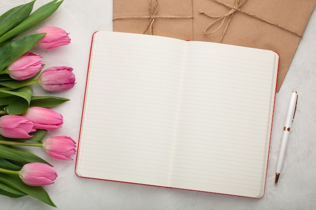 Blank note pad with pen and tulips.