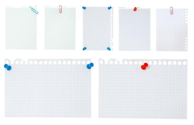 白で隔離の空白のメモ用紙と赤いペーパークリップ