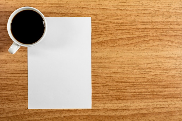 Blank note paper and a coffee cup on wooden desk. - blank space for advertising text.