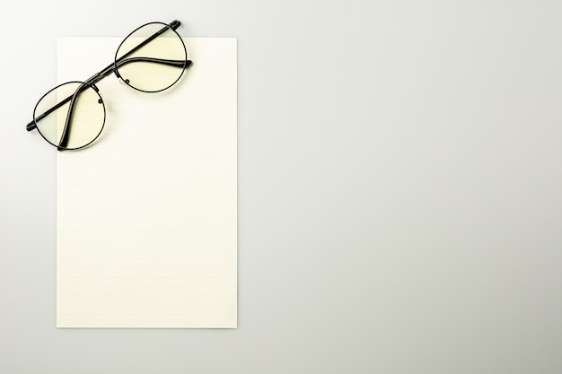 Blank note paper and glasses on grey desk background