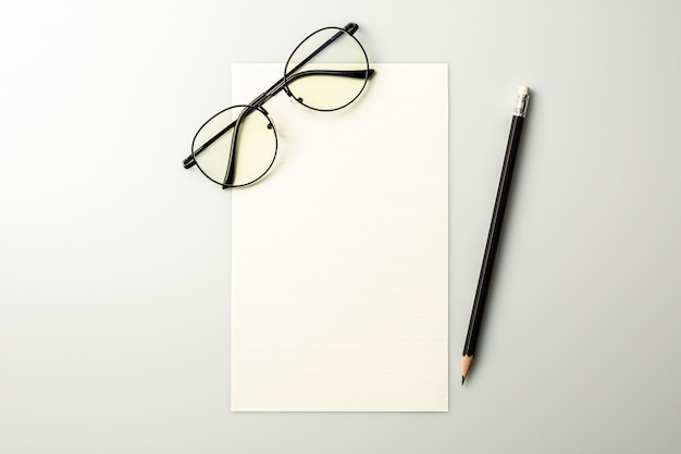 Blank note paper and a pencil on grey desk