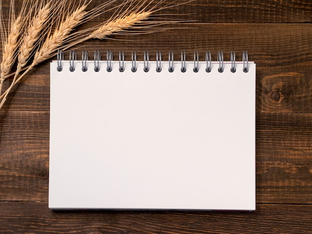 Blank note paper and wheat stalks on wooden background
