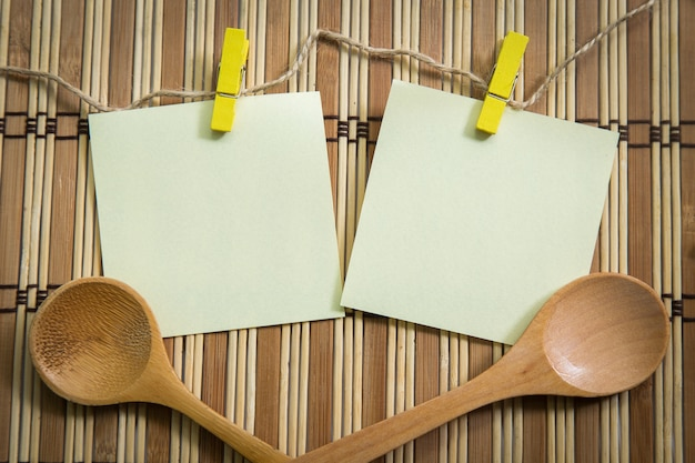 Blank note paper with wooden spoon on wooden background, cooking concept.