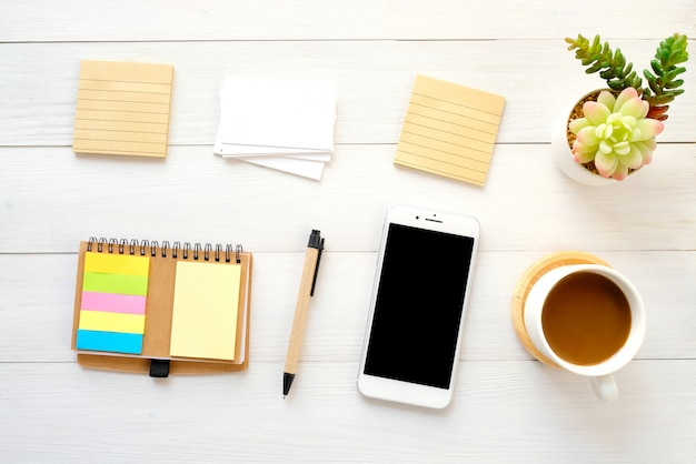 Blank note papers, business card, smart phone, pen and coffee on white