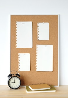 Blank note papers on cork board and clock on wood table