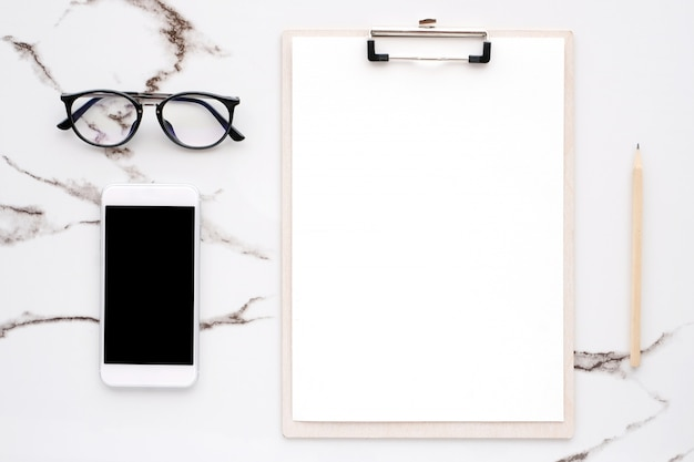 Blank note papers, smart phone, pencil and eyeglasses on white marble