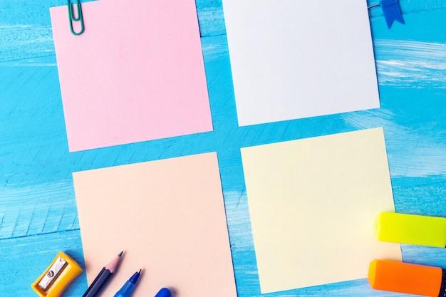文房具のオフィスと白紙のメモシートは、ペン、鉛筆、ペーパークリップを提供します。学校のコンセプトに戻る