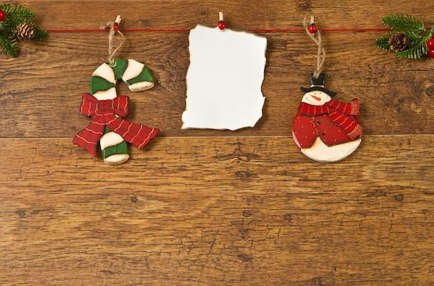 木製の背景にクリスマスの装飾と白紙のメモ