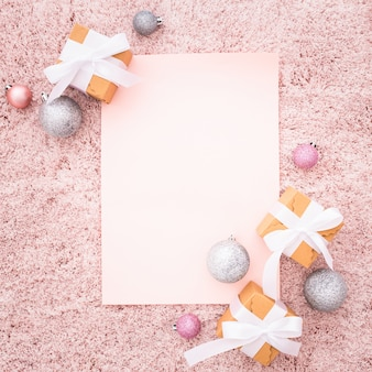 Blank note with christmas ornaments on a pink textured carpet