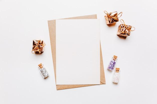 Пустая записка с конвертом, подарками и золотыми звездами блеска на белом