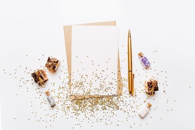 Пустая записка с конвертом, подарками, ручкой и золотыми звездами блеска на белом