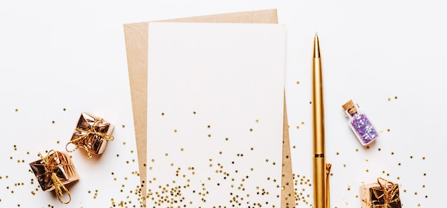 Blank note with envelope, gifts, pen and gold glitter stars on white background