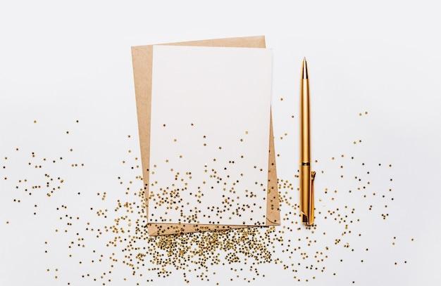 Пустая записка с конвертом, ручкой и звездами золотой блеск на белом фоне