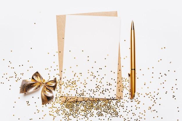 Пустая записка с конвертом, ручкой и золотыми звездами блеска на белом