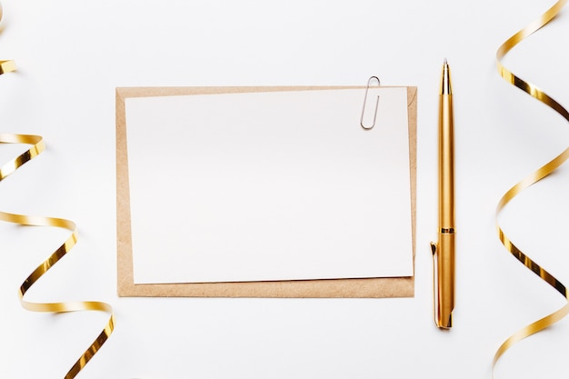 Пустая записка с конвертом, ручкой, подарками и золотой лентой на белом фоне