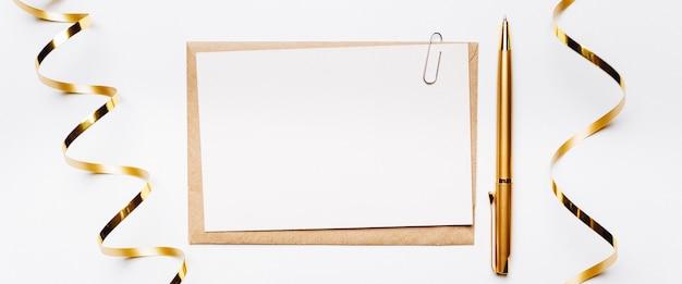 Пустая записка с ручкой и золотой лентой на белом фоне