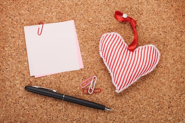 Blank note with toy heart on wooden cork board