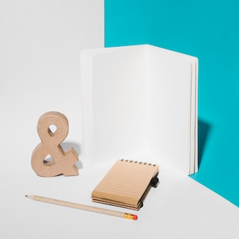 Blank notebook; ampersand symbol; pencil; and spiral notepad on background