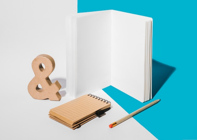 Blank notebook; ampersand symbol; pencil; and spiral notepad on white and blue background