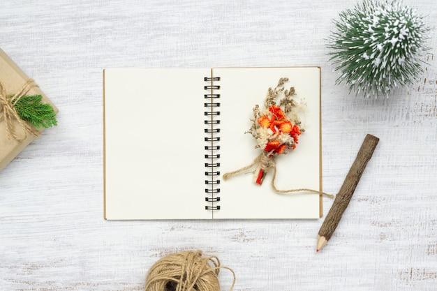 Пустой блокнот и рождественские украшения на белом дереве