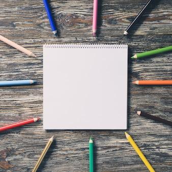 空白のノートブックと木製のテーブルにカラフルな鉛筆。用紙の背景。