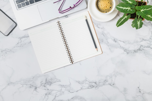 Пустой блокнот и ноутбук с горячим кофе на фоне мраморного стола, вид сверху и копировальное пространство