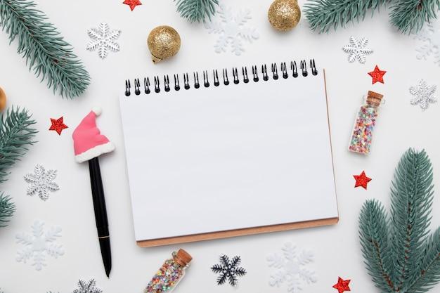 Пустой блокнот и ручка с плоским лежали среди новогоднего рождественского декора, изолированного на белом