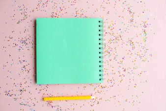 Blank notebook and pen with confetti
