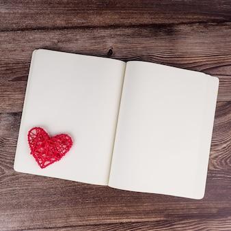 Пустые блокнот и ручка с красным украшением в форме сердца на фоне деревянного стола. свадьба, романтика и счастье.